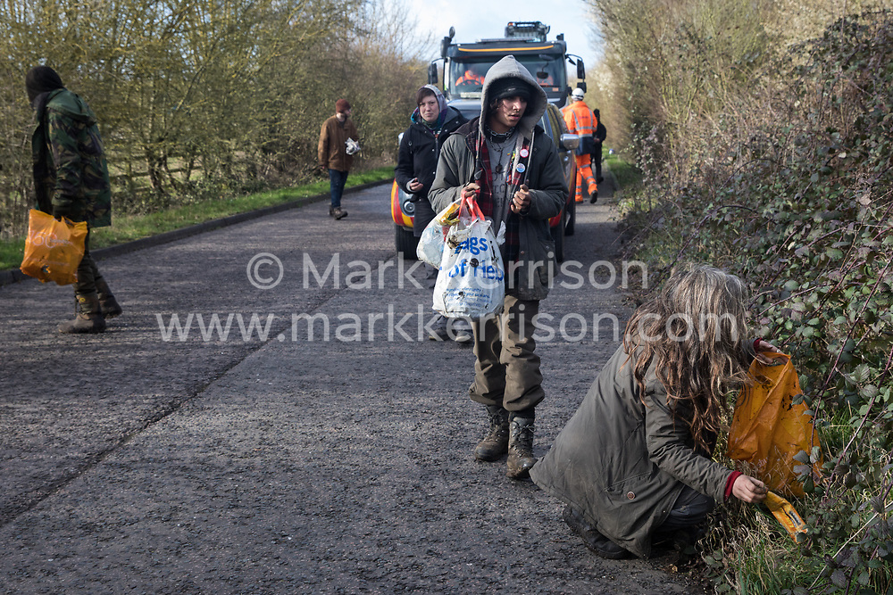Denham, UK. 11 February, 2020. Environmental activists from Extinction Rebellion, Stop HS2 and Save the Colne Valley pick up litter as they 'slow walk' in front of a large truck transporting a JCB forklift truck to a HS2 site at Denham in the Colne Valley. Contractors working on behalf of HS2 are rerouting electricity pylons through a Site of Metropolitan Importance for Nature Conservation (SMI) in conjunction with the high-speed rail link.