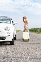 Woman looking at broken down car while pulling luggage on country road