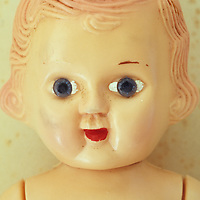 Head and chest of vintage naked girl doll with fixed big staring blue eyes slightly crossed and red lips