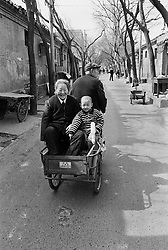 Family travelling in small bicycle cart in a hutong in Beijing China