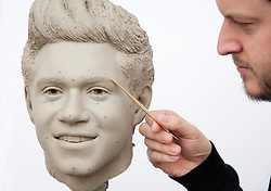 """© Licensed to London News Pictures. 15/02/2013. London, UK Sculptor Dave Burks works on the clay head of Niall Horan. Madame Tussauds today released pictures of sculptors working on the life-like clay heads of the five members of pop band """"One Direction ' The clay heads will be used to create the moulds for their new wax figures. Niall, Liam, Louis, Harry and Zayn have been closely involved in the creation process giving the creative team two sittings at which hundreds of measurements were taken to ensure total accuracy. The clay heads will now be used to make the moulds for the final wax figures, which will be revealed in London. Photo credit : Madame Tussauds /LNP"""