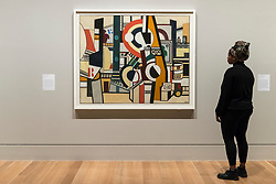"© Licensed to London News Pictures. 04/06/2018. LONDON, UK. A gallery staff member views ""Discs in the City, Les Disques dans la ville"", 1920, by Fernand Léger at a preview of ""Aftermath:  Art in the wake of World War One"" at Tate Britain.  The exhibition marks 100 years since the end of the First World War, exploring the impact of the conflict on British, German, and French art in over 150 works from 1916 to 1932.  The show runs 5 June to 23 September 2018.  Photo credit: Stephen Chung/LNP"
