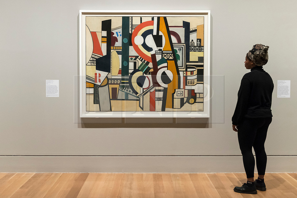 """© Licensed to London News Pictures. 04/06/2018. LONDON, UK. A gallery staff member views """"Discs in the City, Les Disques dans la ville"""", 1920, by Fernand Léger at a preview of """"Aftermath:  Art in the wake of World War One"""" at Tate Britain.  The exhibition marks 100 years since the end of the First World War, exploring the impact of the conflict on British, German, and French art in over 150 works from 1916 to 1932.  The show runs 5 June to 23 September 2018.  Photo credit: Stephen Chung/LNP"""