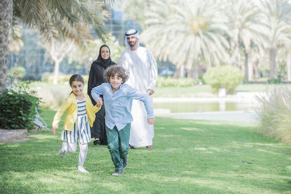 Brother and sister hold hands and run through a park as their mother and father look on from behind. Traditional Arab Emirati family with mother and father wearing thaabe, the woman an abaya and hijab, the man a kandura, ghutra and agal. Dubai, United Arab Emirates.