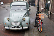 Een besteleend bij een oranje fiets.<br /> <br /> An old Acadiane is parked nearby a orange bike.