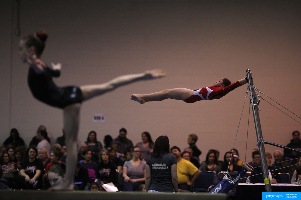 A young gymnasts performs on the uneven bars, (background), as a competitor performs on the balance beam, (foreground), during competition at the 21st American Invitational 2014 competition at the XL Centre. Hartford, Connecticut, USA. USA. 31st January 2014. Photo Tim Clayton