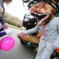 Henry McCormick tries not to scare off the kids while wearing his T-rex head as he passes out candy during Tuesday's annual Truc=nk or Treat along Jeffereson Street in Tupelo.