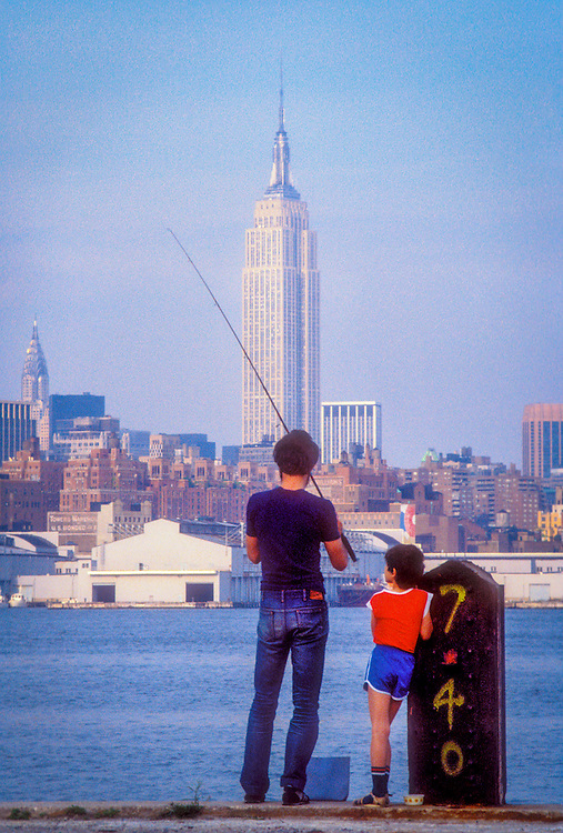 A man and boy fish from a pier on the New Jersey side of the Hudson River with the Empire State Building and Manhattan skyline in the background.