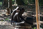 Tété fabrique sculpte un pot dans un tronc de bambou. Il servira à conserver le miel sauvage qu'il a récolté. Sur son dos, un petit garçon qui n'est pas le sien. Il se nomme Outchou. Chez les Jarawas, les femmes et les hommes s'occupent des enfants, les leurs et ceux des autres.