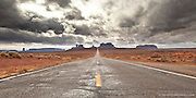 Unsettled weather hangs over the open road leading into Monument Valley.  Navajo Tribal Nation, Arizona.