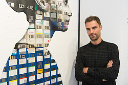 © Licensed to London News Pictures. 13/09/2018. London, UK. Artist NICK GENTRY poses with his work titled Guess Who, 2018 Nick paints portraits on top of obsolete technological materials such as VHS cassettes and floppy disks that contain people's memories. His work is part of a joint exhibiton with South Korea artist SEO YOUNG-DEOK at the Opera Gallery. Photo credit: Ray Tang/LNP