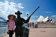 "Child (6 years old) with ""human statue"" busker, Sydney Opera House in background. Sydney, Australia"