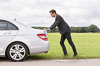 Full length side view of young businessman pushing broken down car at countryside