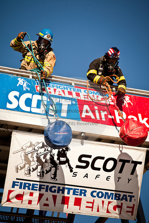 Two firefighters hoist a 42-pound firehose up six stories wearing full firefighting gear and working against the clock during the international finals of the Firefighter Combat Challenge on November 18, 2011 in Myrtle Beach, South Carolina.