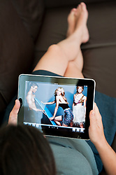 close up of woman using iPad digital tablet computer to look at online Net-a-Porter shopping catalogue