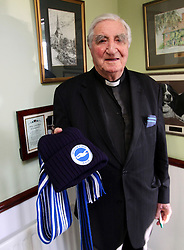 "© Licensed to London News Pictures. 01/02/2012. Uckfield, UK. BILL PETERS at home holding a scarf and hat for the team Brighton and Hove Albion fro whom he played before WWII. Canon Bill Peters of Uckfield, the only chaplain who served in the Second World War still working, is celebrating his 70th year in the church as he approaches his 93rd birthday this year. It has been 67 years since he signed up with the Royal Army Chaplains Department. Canon Peters, who lives in Uckfield is a widower of 10 years and a grand-father of two, He claims he still has a lot left to achieve and said: ""If anybody wants to get married, and the parish is happy, then I do them. I do more weddings than funerals. I have been a priest for 70 years this year and I have spent all that time in Sussex, except when I was in the army and canon of a cathedral."" Photo credit : Ron Hill/LNP NOTE TO EDITORS - WORDS AVAILABLE HERE: http://tinyurl.com/73zbhmu"