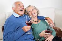 Happy senior couple with red wine glasses while sitting on sofa at home