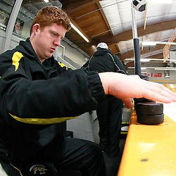 AURORA, ON - Feb 15 : Ontario Junior Hockey League Game Action between the Pickering Panthers and the Aurora Tigers, Assistant Equipment Manager Andrew Walter prepares the pucks for warm-up.<br /> (Photo by Brian Watts / OJHL Images)