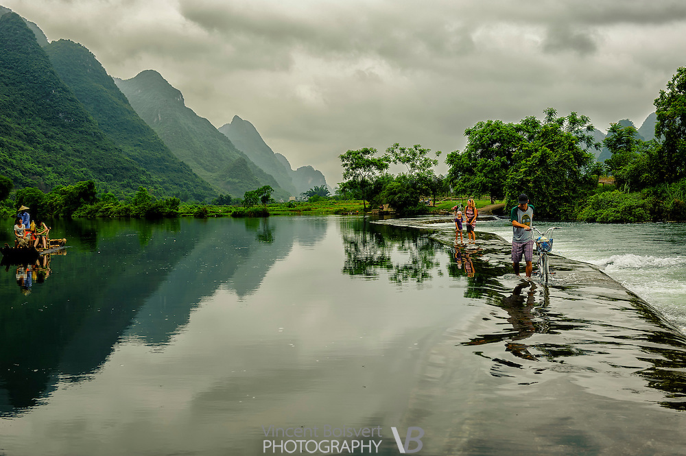 Tourists Crossing Yulong River on a concrete dam, Yangshuo Area, China