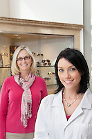 Portrait of happy mid adult optician and customer wearing glasses