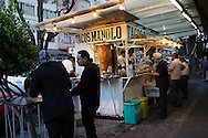 Standing at the cournter and street side tables to eat customers at the popular Tacos Manolo.
