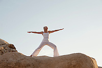 Mature woman in warrior 2 yoga pose on the rocks.<br />