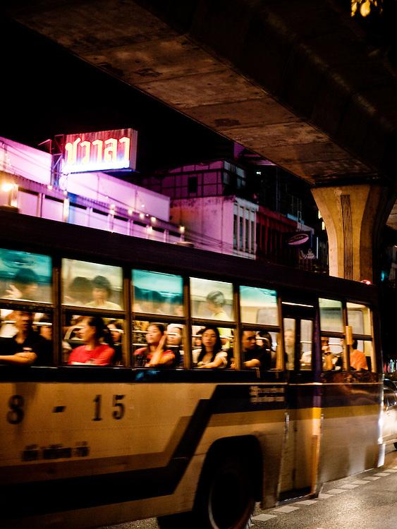 Bus traveling on Sukhumvit Road under the skytrain passes by Chavala Turkish Bath.