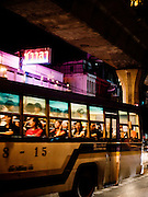 Bus traveling on Sukhumvit Road under the skytrain passes by Chavala Turkish Bath.