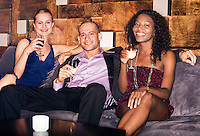Man with two women sitting on couch in bar