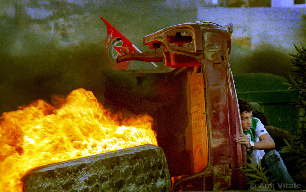 A Palestinian protester hides from Israeli soldiers behind a burning tire and car as protests flared again near the West Bank town of Ramallah Wednesday, October 11, 2000.  (Photo by Ami Vitale)