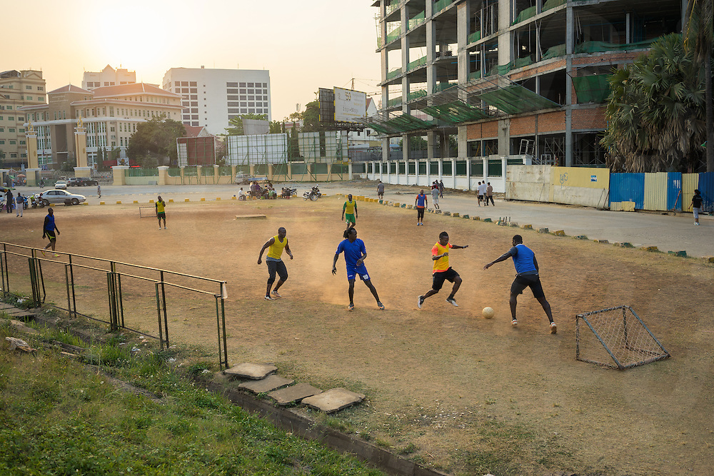 """March 13, 2014 - Phnom Penh. Amateur and professional football players from the """"San Siro Football Association"""" play football near Olympic Stadium, Phnom Penh. These friendly games take place on a daily basis and are an integral part of the social life of many African men living in Phnom Penh. © Thomas Cristofoletti / Ruom."""
