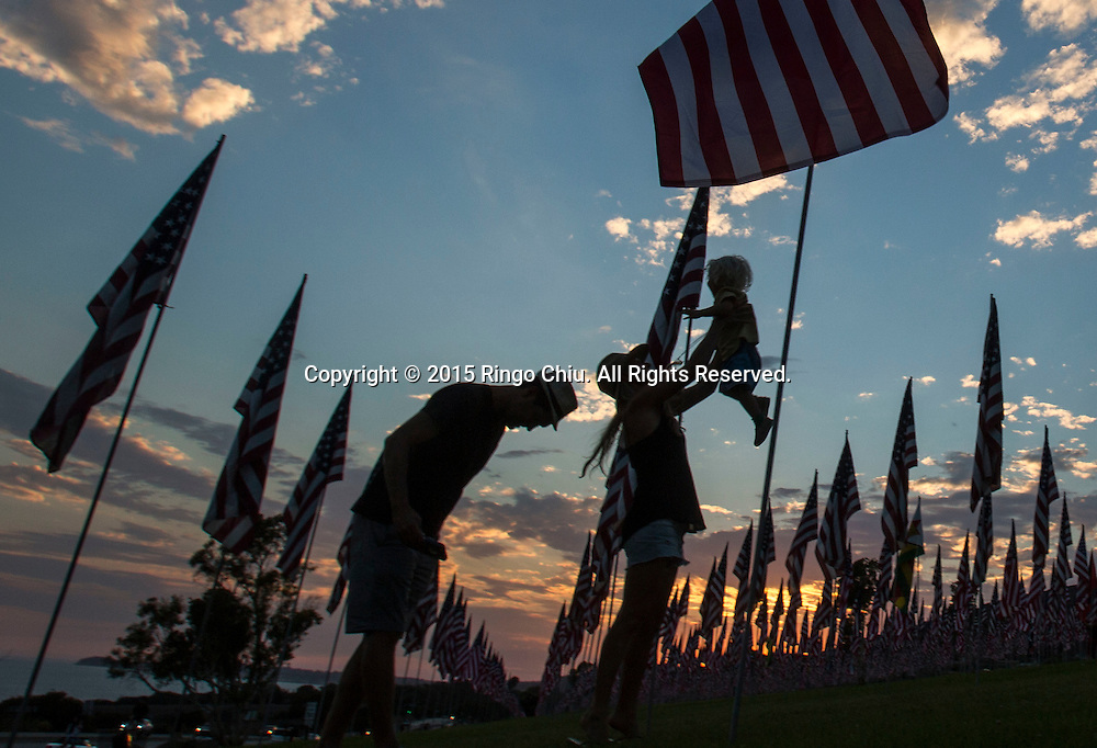 People walk amongst 3,000 US flags are displayed at Pepperdine University to mark the 14th anniversary of the 9/11 terror attack, September 10, 2015 in Malibu, California.  Photo by Ringo Chiu/PHOTOFORMULA.com)
