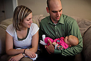 Benjamin Tippetts, 27, is looking over his newborn daughter with his wife, inside their home in La Crosse, WI, USA, where he works as a freelance financial advisor. Benjamin has been an Army infantryman in Fallujah, fighting in the 2nd battle in 2004.