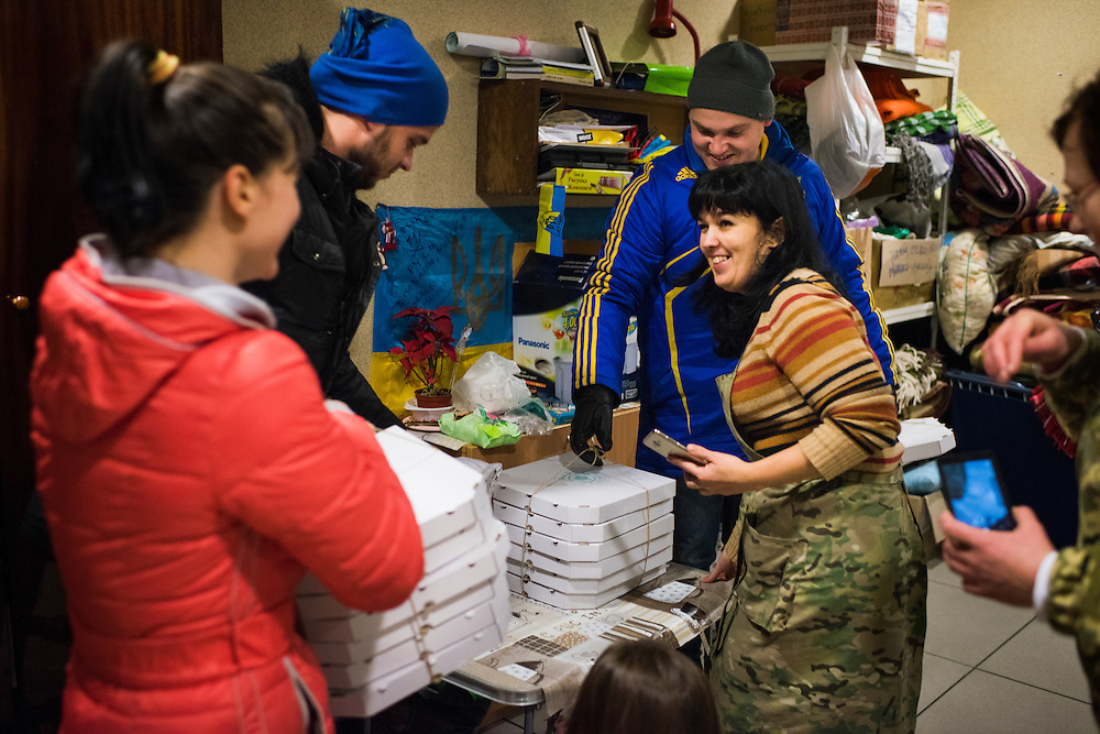 Employees of Veterano Pizza, including veteran Artyom Rudenko, center, blue jacket, deliver donated pizzas to volunteers at Kiev-Pasazhyrs'kyi train station on January 24, 2016 in Kiev, Ukraine. The pizzas, which are donated by customers of the restaurant, will be distributed to soldiers as they deploy via train to the front lines in Eastern Ukraine. (Pete Kiehart for The New York Times)