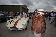 A woman dressed in vintage clothing walks next to a classic racing car at the Goodwood Revival in Chichester, England   Friday, Sept. 9, 2016 The historic motor racing festival celebrates the mid-20th-century golden era of the racing circuit and recreates the atmosphere from the 1950s and 1960s.(Elizabeth Dalziel)