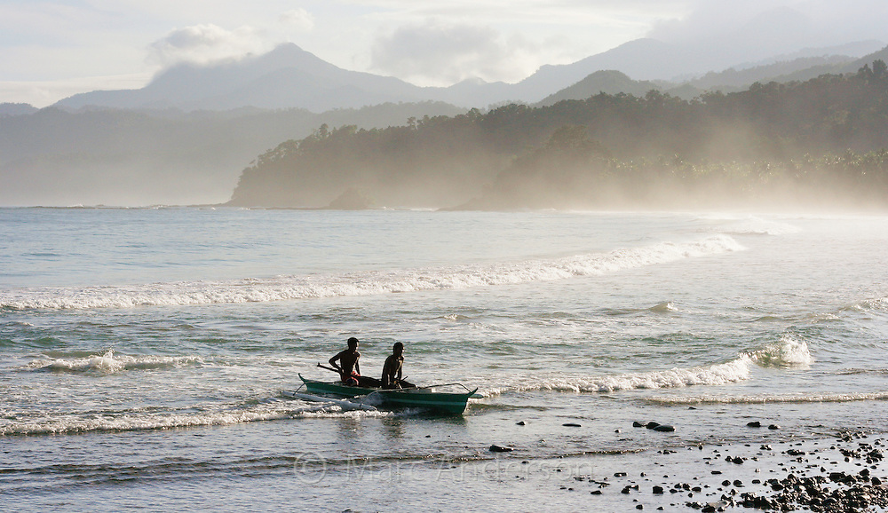 Two men bringing a small boat ashore to a beautiful beach, Sabang, Palawan, Philippines