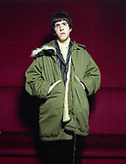 Young man standing against red wall wearing a parka.