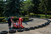 A young girl gets some assistance while driving a go cart at the Sarajevo Zoo. The culture is still a conservative patriarchal one where traditional roles for men and women hold true.