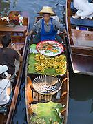 floating market; food vendor in narrow rowboat pulls boat between 2 boats of tourists; Damnoen Saduak; Thaiiland
