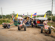 21 FEBRUARY 2014 - KHLONG CHIK, PHRA NAKHON SI AYUTTHAYA, THAILAND: Farmers' tractors parked on the side of Highway 32 during a motorcade headed to Bangkok. About 10,000 Thai rice farmers, traveling in nearly 1,000 tractors and farm vehicles, blocked Highway 32 near Bang Pa In in Phra Nakhon Si Ayutthaya province. The farmers were traveling to the airport in Bangkok to protest against the government because they haven't been paid for rice the government bought from them last year. The farmers turned around and went home after they met with government officials who promised to pay the farmers next week. This is the latest blow to the government of Yingluck Shinawatra which is confronting protests led by anti-government groups, legal challenges from the anti-corruption commission and expanding protests from farmers who haven't been paid for rice the government bought.    PHOTO BY JACK KURTZ