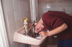 Teenage girl washing hair in bathroom basin,
