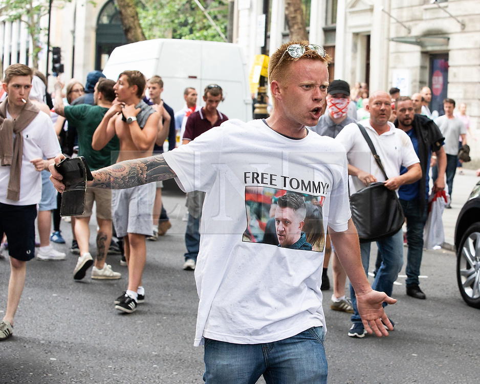 © Licensed to London News Pictures. 09/06/2018. London, UK. Supporters of EDL founder Tommy Robinson ( real name Stephen Yaxley-Lennon ) clash with police in Westminster during a demonstration on Whitehall in Westminster after Robinson was convicted of Contempt of Court . Robinson was already serving a suspended sentence for Contempt of Court over a similar incident , when he was convicted on Friday 25th May 2018 . Photo credit: Joel Goodman/LNP