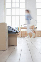 Woman walks across loft apartment blurred motion
