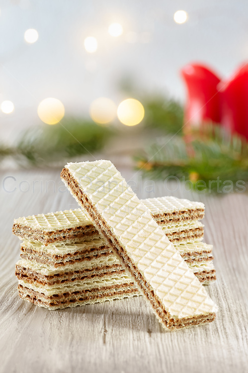 Stack of wafer biscuits filled with hazelnuts cream with winter holidays lights bokeh in the background.