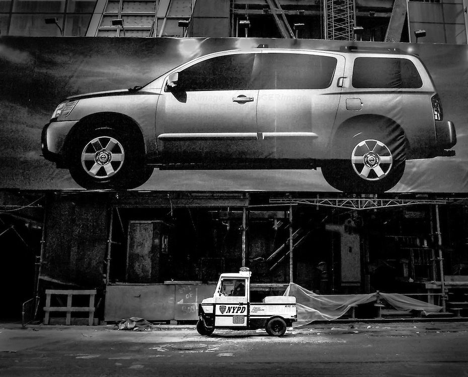 Dull daylight afternoon shot taken in Manhattan New York just off Times Square.  Large Nissan Hoarding on consrtuction site dwarfing NYPD traffic trike.