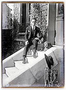 young man in suite with dog sitting on stairs early 1900s