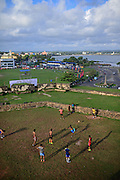 Street soccer game in improvised field next to UNESCO World Heritage, Galle Fort, during Binara Full Moon Poya Day.