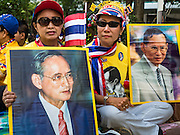 05 DECEMBER 2015 - BANGKOK, THAILAND:  Women a portrait of the King of Thailand in the plaza at Siriraj Hospital on the 88th birthday of Bhumibol Adulyadej, the King of Thailand. Hundreds of people crowded into the plaza hoping to catch a glimpse of the revered Monarch. The King has lived at Siriraj Hospital off and on for more than four years.    PHOTO BY JACK KURTZ