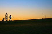A Sydney sunset with person walking in a park.