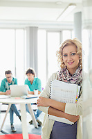 Portrait of beautiful businesswoman holding files with colleagues working in background at creative office